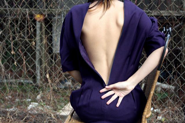 Femme avec le dos dénudé par sa robe entrouverte mains sur le bas du dos